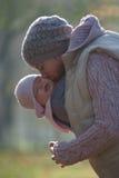Mutter, die draußen Baby umarmt Stockbilder
