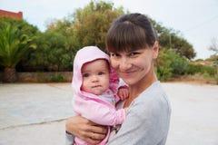 Mutter, die draußen ihre kleine Tochter umarmt Lizenzfreie Stockfotos