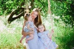 Mutter, die draußen zwei Töchter umarmt Stockbilder
