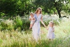 Mutter, die draußen zwei Töchter umarmt Stockbild