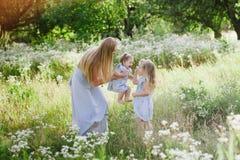 Mutter, die draußen zwei Töchter umarmt Lizenzfreie Stockfotografie