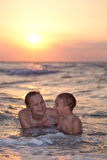 Mutter, die ein Abendschwimmen mit ihrem Sohn genießt Lizenzfreies Stockfoto