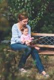 Mutter, die ein Buch ihre kleine Tochter liest Lizenzfreies Stockfoto