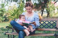 Mutter, die ein Buch ihre kleine Tochter liest Lizenzfreie Stockfotos