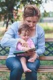 Mutter, die ein Buch ihre Tochter liest Lizenzfreie Stockfotografie