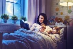 Mutter, die ein Buch liest Stockbild