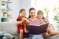 Mutter, die ein Buch zu den T?chtern liest stockfotografie