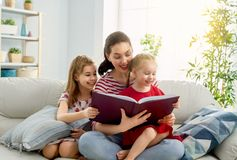 Mutter, die ein Buch zu den T?chtern liest stockbilder