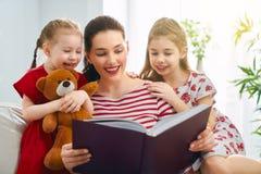 Mutter, die ein Buch zu den T?chtern liest lizenzfreies stockfoto