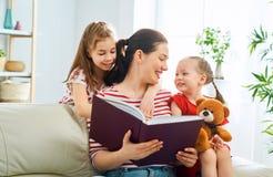 Mutter, die ein Buch zu den T?chtern liest stockbild