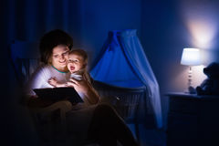 Mutter, die ein Buch zum kleinen Baby liest Lizenzfreies Stockfoto