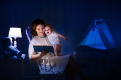 Mutter, die ein Buch zum kleinen Baby liest Stockbild