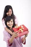 Mutter, die ein Geschenk von ihrer Tochter öffnet Stockbilder