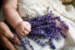 Mutter, die ein Kind und einen Blumenstrauß des Lavendels hält stockfoto