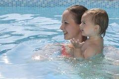 Mutter, die ein Pool mit Kind genießt Lizenzfreie Stockfotografie