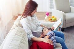 Mutter, die eine Geschichte zu ihrem Sohn liest Stockfotos
