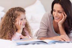 Mutter, die eine Gutenachtgeschichte für ihre Tochter liest Lizenzfreies Stockbild