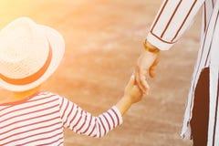 Mutter, die eine Kind-` s Hand hält Stockbilder