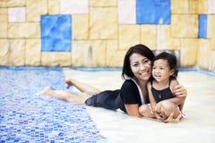 Mutter, die eine Qualitätszeit am Swimmingpool hat Lizenzfreies Stockbild