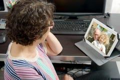 Mutter, die einen entfernten Anruf auf Internet macht lizenzfreies stockbild