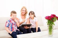 Mutter, die einen Tablet-PC verwendet Stockfotos
