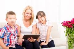 Mutter, die einen Tablet-PC verwendet Stockfotografie