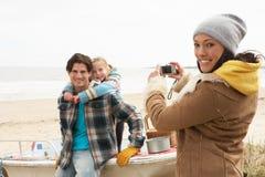 Mutter, die Familien-Fotographie auf Winter-Strand nimmt Stockfoto
