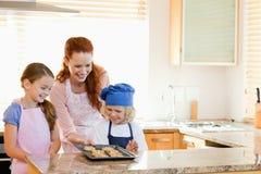 Mutter, die fertige Plätzchen ihren Kindern darstellt Stockfotografie