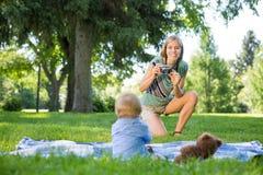 Mutter, die Foto des Babys im Park macht Lizenzfreie Stockfotografie