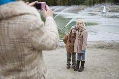 Mutter, die Foto von Kindern vor Brunnen macht Stockfotografie