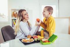 Mutter, die Frühstück für ihre Kinder macht Lizenzfreie Stockfotografie