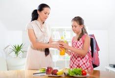 Mutter, die Frühstück für ihre Kinder macht Lizenzfreies Stockbild
