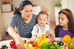 Mutter, die Frühstück für ihre Kinder macht Stockfotografie