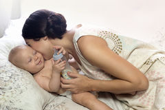 Mutter, die frohes Kind umarmt Nach der Fütterung Stockfotos