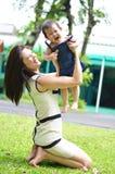 Mutter, die glückliches Gesicht des Babys hält Stockbilder
