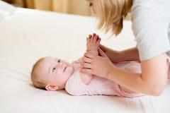 Mutter, die Gymnastikbaby massiert oder tut Lizenzfreie Stockfotografie