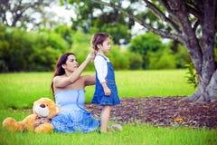 Mutter, die Haar ihrer Tochter tut lizenzfreie stockfotos