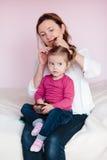 Mutter, die Haar ihrer Tochter tut Stockbild