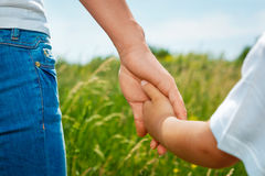 Mutter, die Hand ihres Sohns hält Lizenzfreies Stockbild