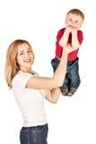 Mutter, die herauf überraschtes Kind wirft Lizenzfreie Stockbilder