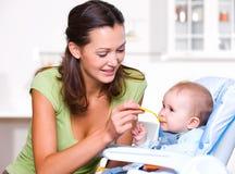 Mutter, die hungriges Schätzchen speist Lizenzfreies Stockfoto