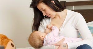 Mutter, die ihr Baby auf Bett stillt stock video