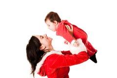 Mutter, die ihr Baby beide gekleidet als Sankt hält Stockbilder