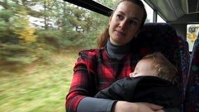 Mutter, die ihr Baby beim mit dem Bus austauschen hält Zufälliger Schuss des Pendlerallein erziehende mutter mit ihrem Baby, das  lizenzfreies stockbild