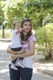 Mutter, die ihr Baby im Park hält stockfoto