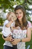 Mutter, die ihr Baby im Park hält lizenzfreie stockfotos