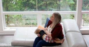 Mutter, die ihr Baby im Wohnzimmer 4k tröstet stock video footage