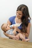 Mutter, die ihr Baby mit der Flasche füttert Stockbilder