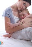 Mutter, die ihr Baby schaukelt Lizenzfreie Stockbilder