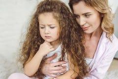 Mutter, die ihr gelocktes beleidigt umarmt stockbilder